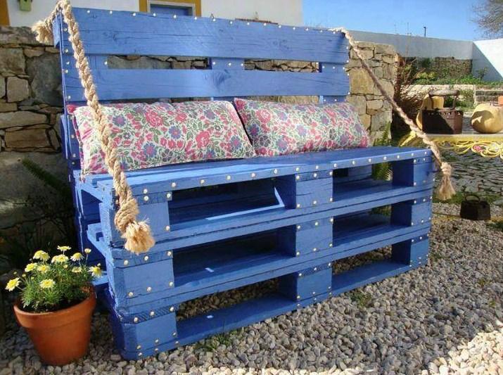 Romantyczna ławeczka z palet pomalowanych na błękitny kolor. Do tego poduszeczki i... czas na relaks!