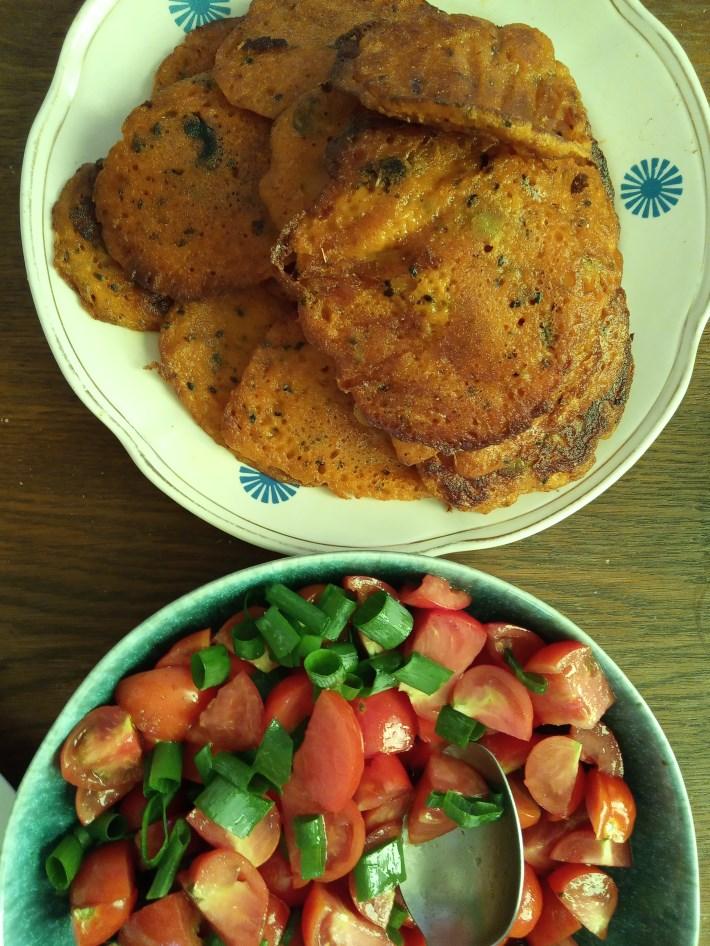 Placki z oliwkami i czarnym sezamem w otoczeniu pomidorków.